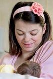 哺乳她新出生的婴孩的产科母亲 免版税库存照片