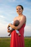 哺乳她的妇女年轻人的婴孩 库存照片