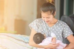 哺乳她的婴孩的美丽的愉快的母亲 免版税库存图片