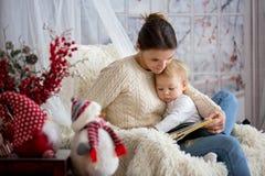 哺乳她的小孩儿子的母亲坐在舒适扶手椅子,冬天 免版税库存图片