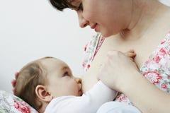 哺乳她的小母亲的婴孩 免版税库存照片