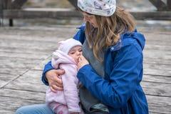 哺乳她的新生儿女孩的母亲在公园 免版税库存图片