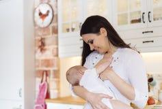 哺乳她的母亲的婴孩 免版税库存图片