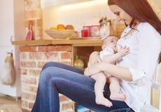 哺乳她的母亲的婴孩 库存照片