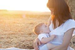哺乳她的男婴的美丽的愉快的母亲室外 免版税图库摄影