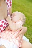 哺乳她的婴孩的妇女户外 免版税图库摄影