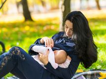 哺乳户外在城市parkland的母亲 免版税图库摄影