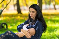 哺乳户外在明亮的parkland的母亲 免版税库存照片