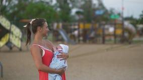 哺乳:年轻母亲哺乳她的城市穿明亮的红色礼服的公园身分的男婴孩子-儿子佩带 股票视频