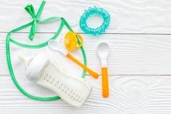 哺养与乳奶或婴儿惯例的孩子搽粉了婴孩牛奶和玩具在木背景顶视图 免版税库存照片