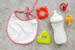 哺养与乳奶或婴儿惯例的孩子搽粉了婴孩牛奶和玩具在灰色背景顶视图大模型 免版税库存照片