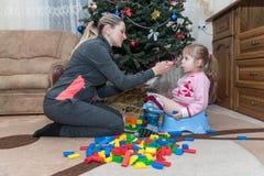 哺养与匙子的妈妈她的四岁女儿,孩子坐罐,妈妈鼓励孩子吃,坐地板 库存照片