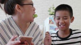 哺养她的母亲的亚裔儿童男孩可口沙拉 股票视频