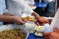 哺养帮助的贫穷的社会问题:哺养饥饿的志愿者在社会:捐赠食物的概念对贫寒 免版税库存图片