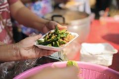 哺养帮助的贫穷的社会问题:哺养饥饿的志愿者在社会:捐赠食物的概念对贫寒 库存照片