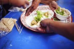 哺养帮助的贫穷的社会问题:哺养饥饿的志愿者在社会:捐赠食物的概念对贫寒 图库摄影