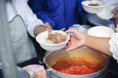 哺养帮助的贫穷的社会问题:生活的概念问题贫寒:志愿者对解除的贫寒的份额食物 免版税图库摄影