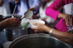 哺养帮助的贫穷的社会问题:生活的概念问题贫寒:志愿者对解除的贫寒的份额食物 库存照片