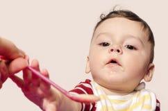 哺养婴儿婴儿食品的母亲手 设法的孩子劫掠匙子 图库摄影