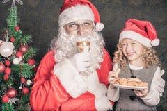 哺养圣诞老人曲奇饼和牛奶的小逗人喜爱的女孩在圣诞节 免版税图库摄影