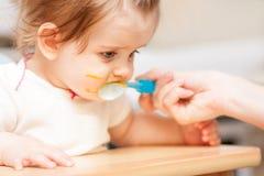 哺养从在蓝色椅子的一把匙子的小女孩 免版税库存图片