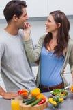 哺养她的丈夫西红柿的可爱的妇女 库存图片