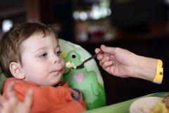 哺养她的儿子煎蛋卷的母亲 图库摄影