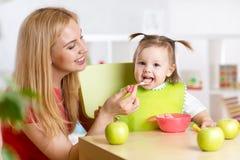 哺养她的孩子健康食物的母亲 免版税库存图片