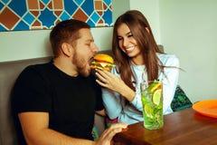 哺养她的男朋友汉堡包的妇女 免版税库存照片