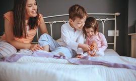 哺养玩偶用曲奇饼的孩子坐在 免版税库存图片