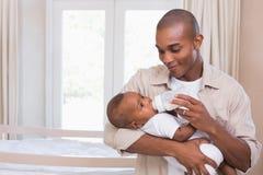 哺养他的男婴瓶的愉快的父亲 免版税库存照片