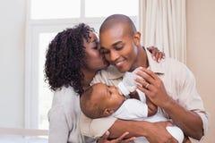 哺养他们的男婴瓶的愉快的父母 免版税库存图片