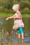 水哺养的鸭子的小女孩 免版税库存照片