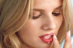 嘴唇护肤 有糖嘴唇的美丽的妇女在嘴唇洗刷 免版税图库摄影