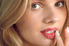 嘴唇护肤 有糖嘴唇的美丽的妇女在嘴唇洗刷 免版税库存照片