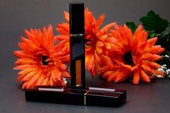 唇膏和橙色花妇女的能使她的看起来美好 库存照片