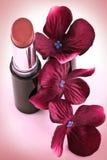 唇膏和绯红色花 免版税库存照片