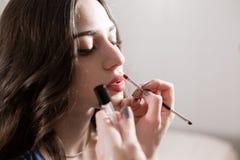 唇膏 创造金发碧眼的女人的化妆师美好的构成塑造 秀丽和温泉中心概念 免版税库存图片