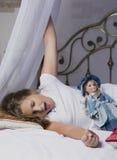 唤醒和舒展在床上的女孩在睡个好觉以后 免版税库存图片
