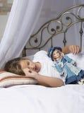 唤醒和舒展在床上的女孩在睡个好觉以后 库存照片