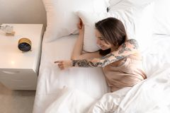 唤醒在床上的年轻女人在早晨 库存照片