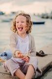 唬弄和使用与在夏天seacost的玩具鸟的愉快的儿童女孩 免版税库存照片