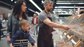 售货员在面包店部门工作在然后包装好家庭母亲和儿子的超级市场小圆面包和 股票录像