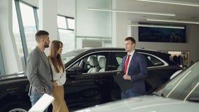 售车行工作者与美好的夫妇有胡子的人和他可爱的妻子谈话,当站立近的豪华汽车时 股票录像