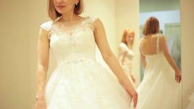 售货员为尝试在新娘精品店的婚礼礼服的美丽的新娘帮助在试装间 股票录像