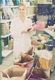 年轻售货员提供选择宠物食品 库存图片