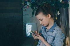 唯一哀伤的青少年的藏品哀叹坐床的一个手机在她的有黑暗的光的卧室在背景中 库存照片