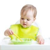 唯一地吃与匙子的儿童女孩 免版税库存图片