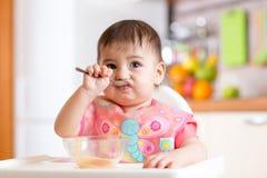 唯一地吃与匙子的儿童女孩 库存图片
