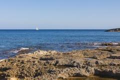 唯一有多岩石的海滩的游艇oon蓝色海 库存图片